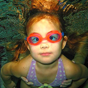 Girl swimming underwater at FLOW Aquatics Swim School with purple swimsuit and pink goggles