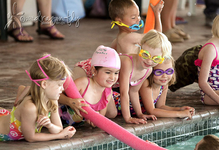 six children in swimming suits gathered at edge of pool at Flow Aquatics Swim School