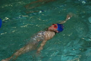 girl-swmming-on-her-back-in-a-blue-swim-cap-and-goggles-at-flow-aquatics-swim-school