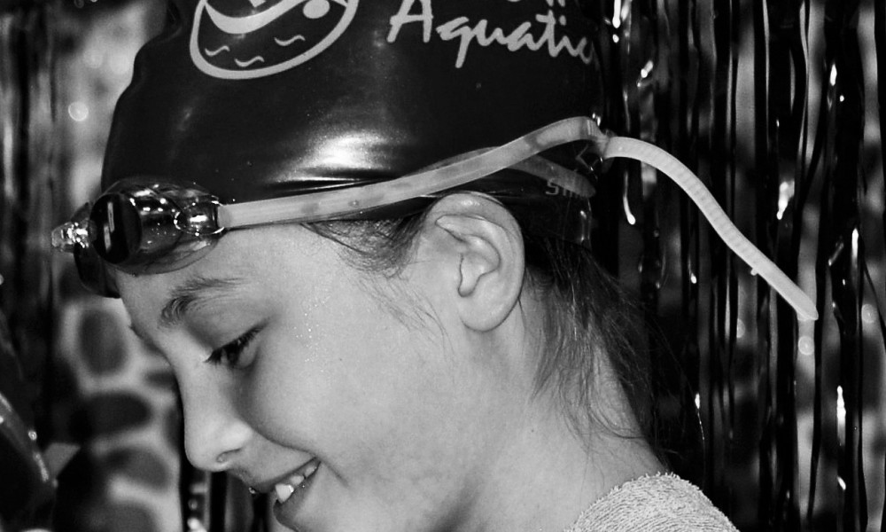 -black-and-white-photo-of-a-swimmer-standing-on-an-awards-stand-at-flow-aquatics-swim-school
